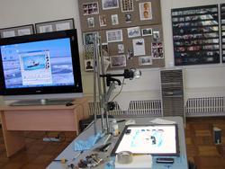 Стол и экран на котором демонстрируется мастер-класс