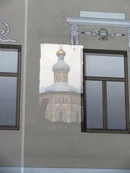 В проеме окна, сквозь банерную ткань виден Петропавловский собор