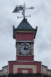 часы на доме и флюгер с изображением всадника