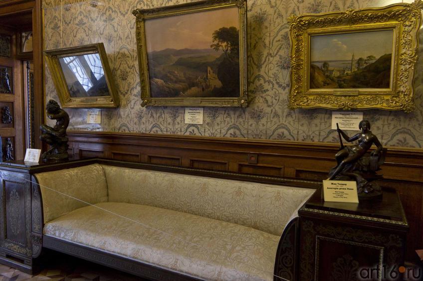 Фрагмент интерьера Ситцевой комнаты: диван, скульптуры и пейзажные полотна на стене