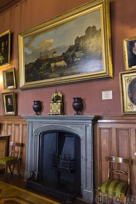 Фрагмент интерьера: камин и стены, увешанные картинами