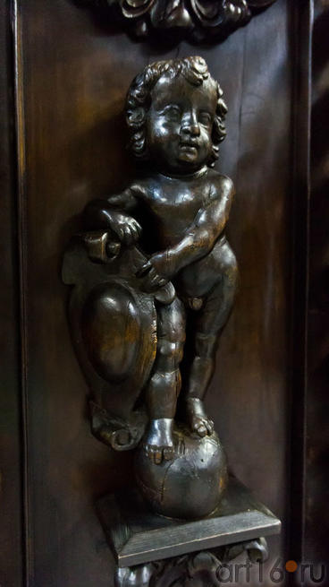 Фигурка ребенка, держащего герб